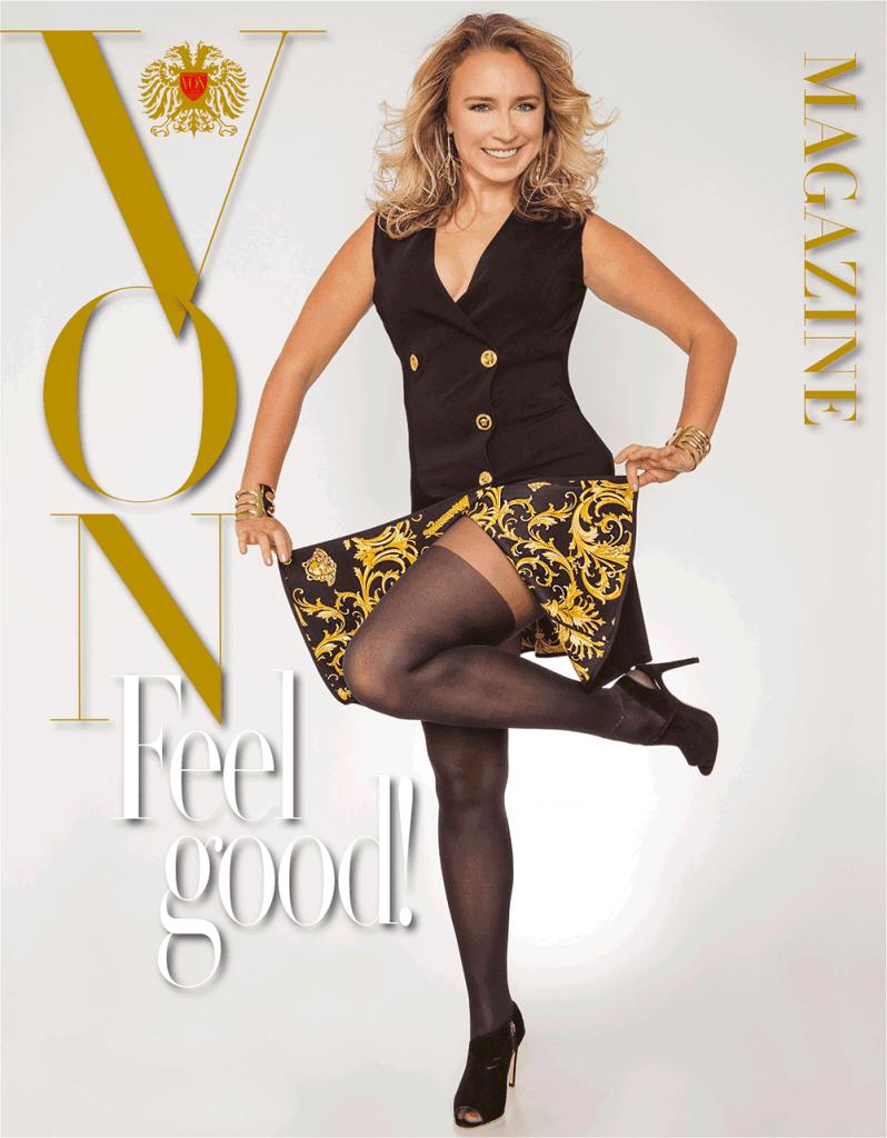VONsociety: Feel Good Challenge zeigt Alona Klammer in einem ärmellosen schwarzen Versace Mantel-Kleid. Sie hält den Saum des Kleides mit beiden Händen hoch; es ist das Innenfutter in goldfarbenem, typischen Versace Muster zu sehen. Sie trägt eine schwarze Strumpfhose und schwarze Stilettos © Paul Harris