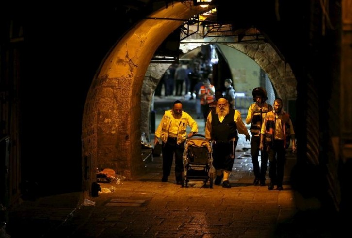 Israeli members of the Zaka Rescue and Recovery team push a baby carriage near the scene where a Palestinian was shot dead after he stabbed and killed two people in Jerusalem's Old City October 3, 2015. A Palestinian man stabbed and killed two people in Jerusalem's Old City on Saturday before police shot him dead, officers said, amid an uptick in violence in the city and occupied West Bank. Palestinian militant group Islamic Jihad issued a statement claiming the attacker as one of its members. REUTERS/Ammar Awad -