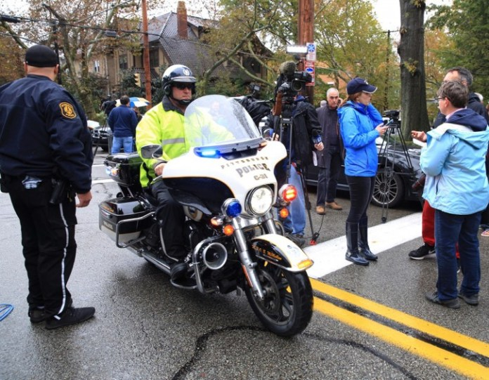 A police officer on motorcycle passes through a roadblock as he responds after a gunman opened fire at the Tree of Life synagogue in Pittsburgh, Pennsylvania, U.S., October 27, 2018.   REUTERS/John Altdorfer