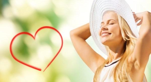 femme avec un chapeau blanc inondée de lumière avec un coeur