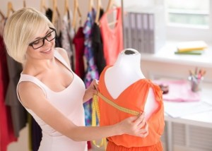 femme qui mesure la ligne d'épaules d'un mannequin de couturier