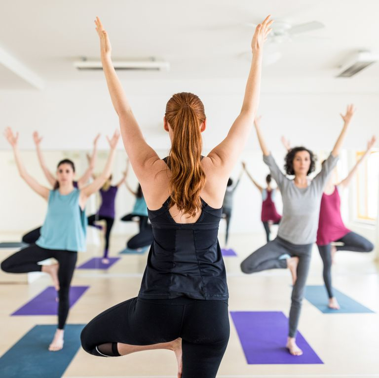 female instructor with yoga class in the gym royalty free image 700718696 1561407106