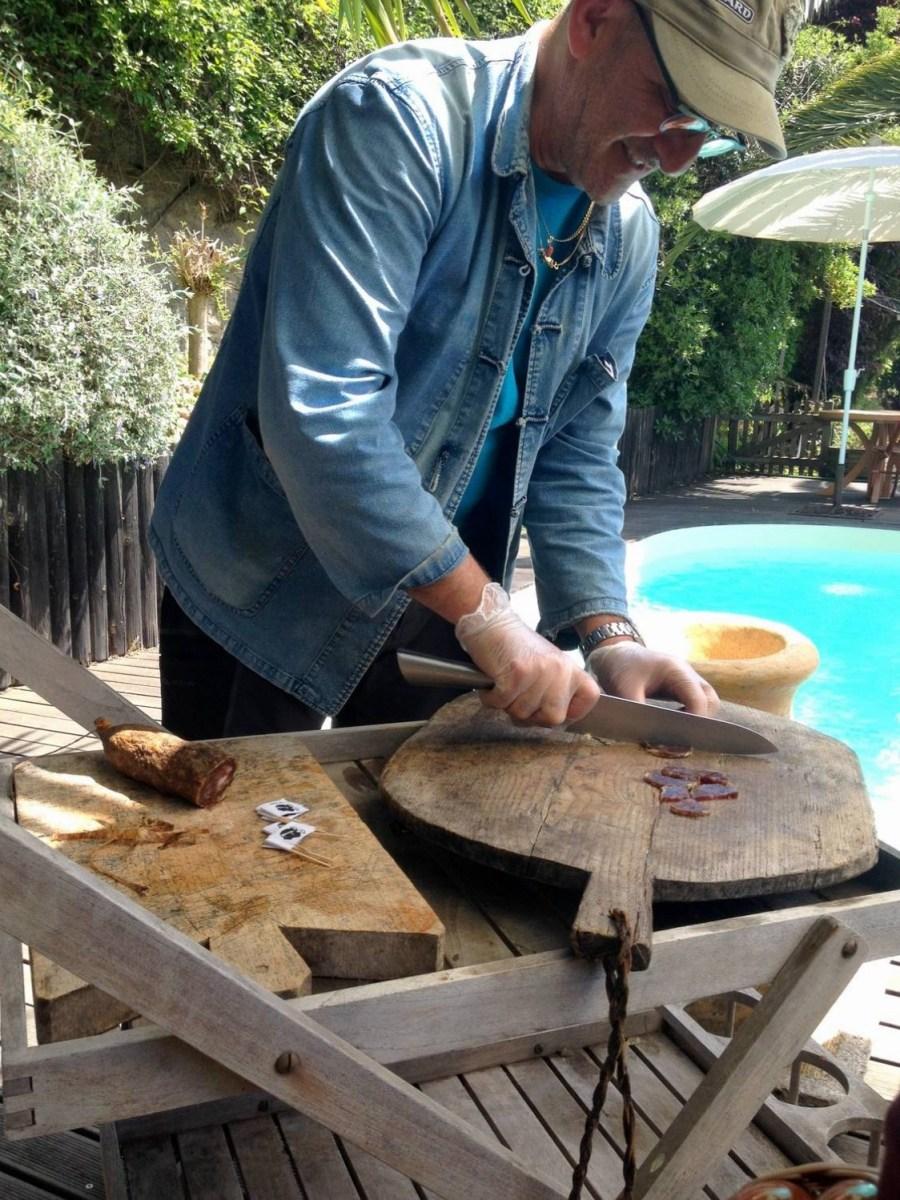 Christian cutting the corsican saucisson at the Villa Guidi - Pila-Canale, Corsica, France