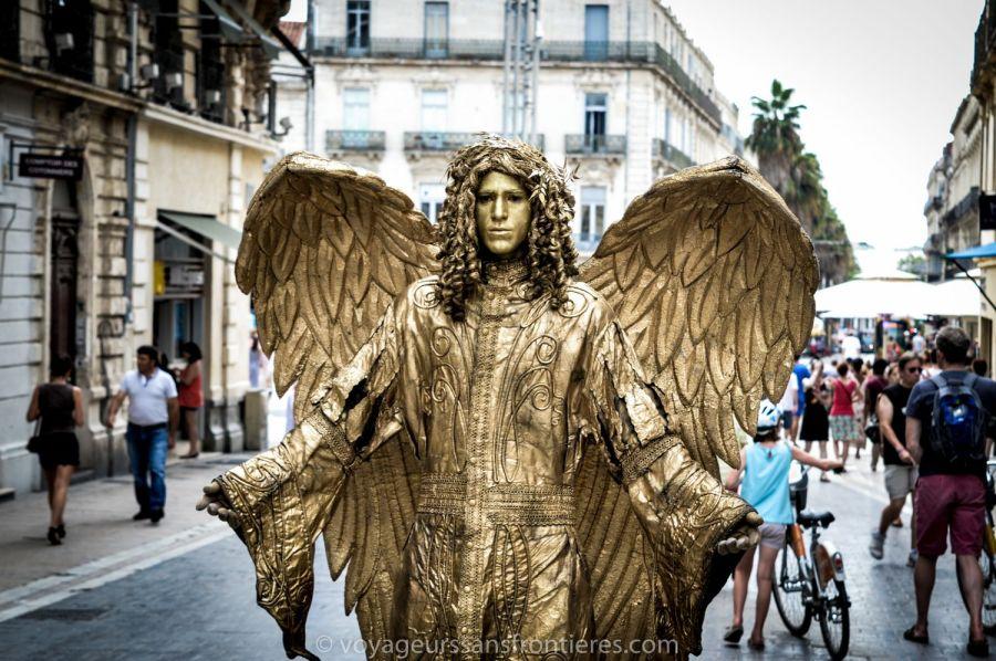 Un artiste de rue déguisé en ange doré dans la Rue de la Loge - Montpellier, France