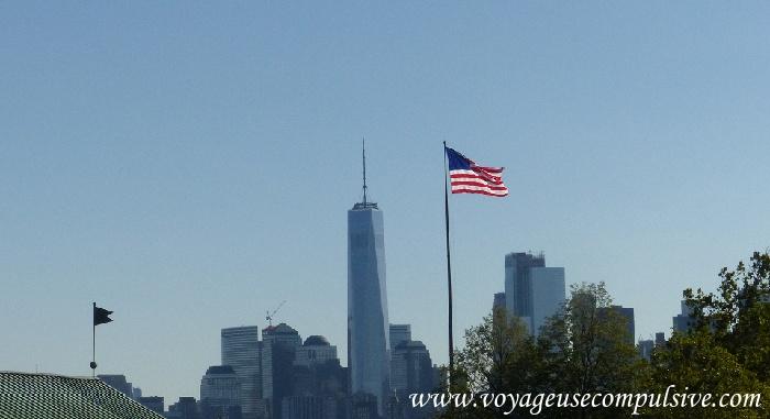 Vue sur le One World et un drapeau américain depuis Ellis Island