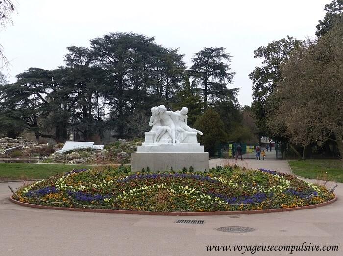 Statue blanche eu milieu d'un cercle rempli de fleur, à l'entrée du parc de la Tête d'Or de la ville de Lyon