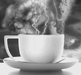 storm in a teacup white cup and plate with spoon on lightening and stormy background