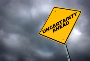 uncertainty ahead traffic sign on gray sky