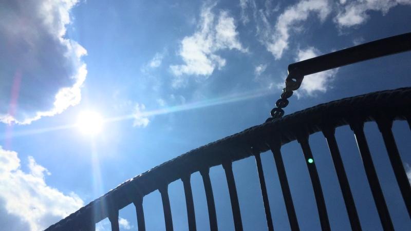 stralende zon aan een blauwe hemel, gezien vanuit een hangstoel