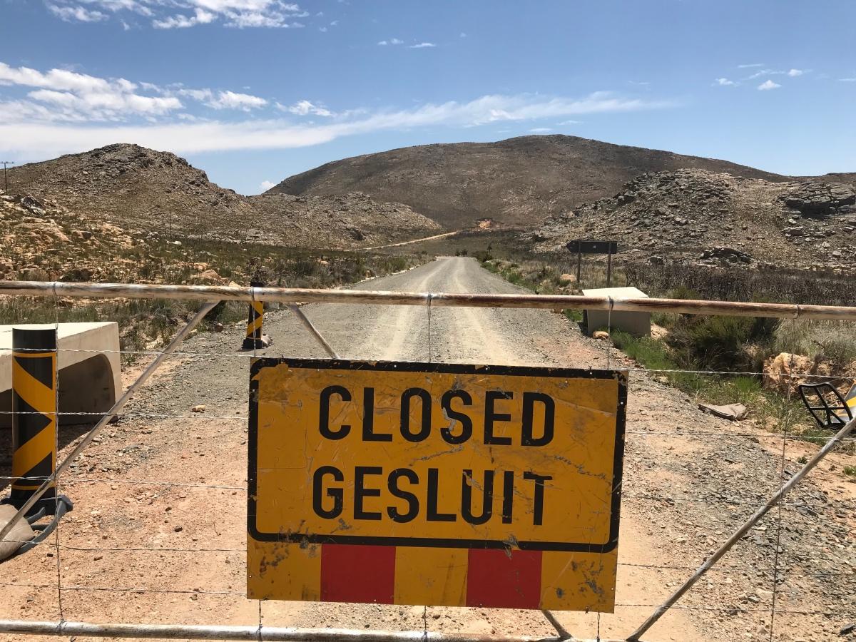 Afrikaans bord op een hek met de tekst 'closed - gesluit'