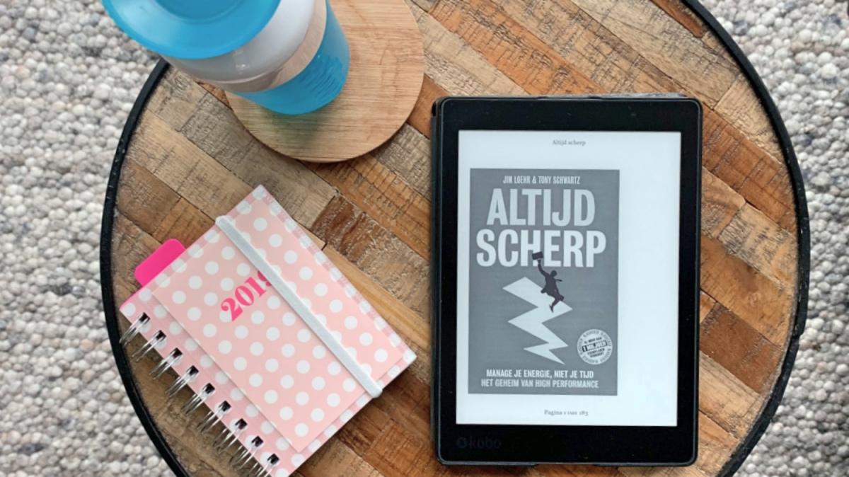 Boek 'Altijd Scherp' van Jim Loehr en Tony Schwartz op de e-reader op een tafeltje met een agenda en een waterfles.