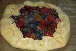 Края теста заворачиваем на ягоды и смазываем взбитым желтком