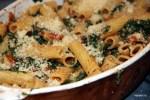 Блюдо с пастой, мангольдом, помидорами и козьим сыром посыпано пармезаном и готово к запеканнию