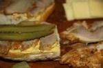 На жареную свинину выкладываем слой тонких ломтиков соленого огурца