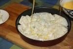 На слой теста кладем брынзу и поливаем яйцом, растительным маслом и водой