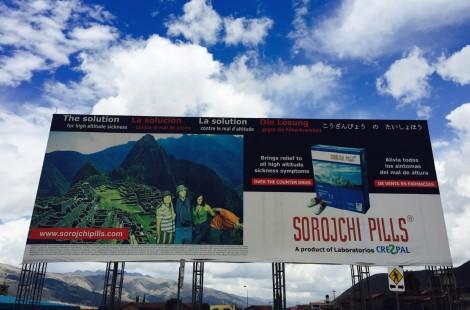 Рекламный щит в Куско демонстрирует опасности восхождения на Мачу-Пикчу без таблеток от горной болезни