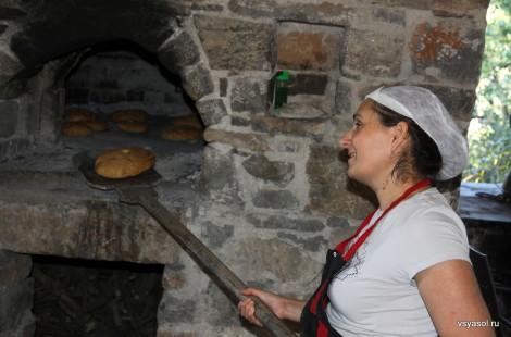Ставрула достает готовый хлеб из печи