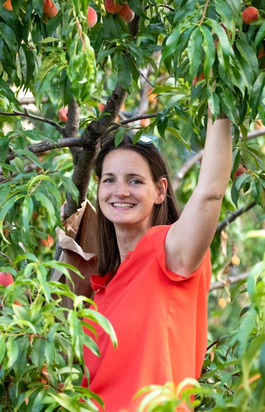 Janet McLaughlin in her backyard peach tree