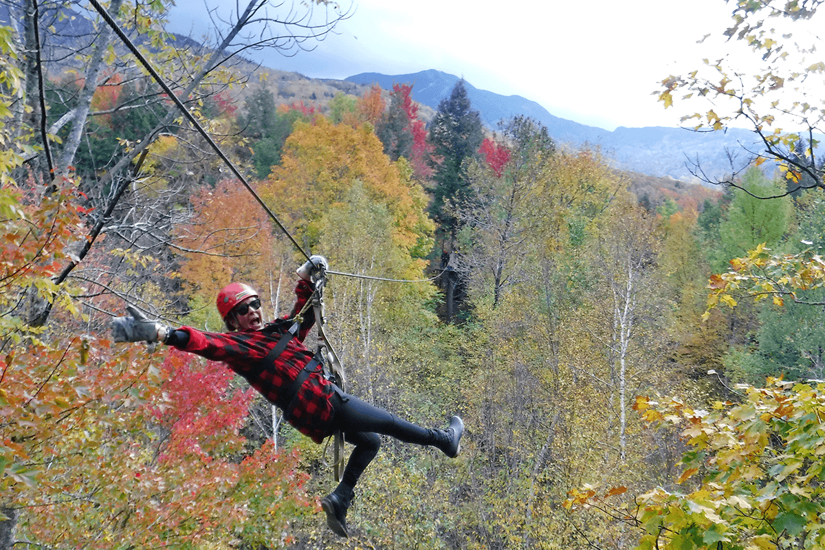 Image of a woman on zipline going down through the trees at Arbortrek at Smuggler's Notch