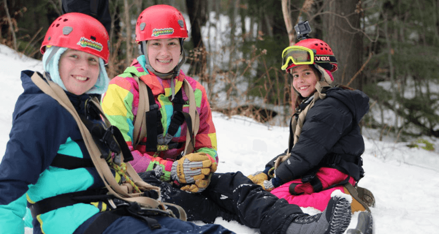 Image of kids sitting on snow at Arbortrek at Smuggler's Notch