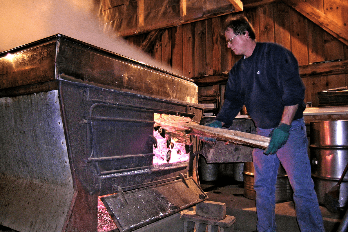Image of man loading the firebox of an evaporator
