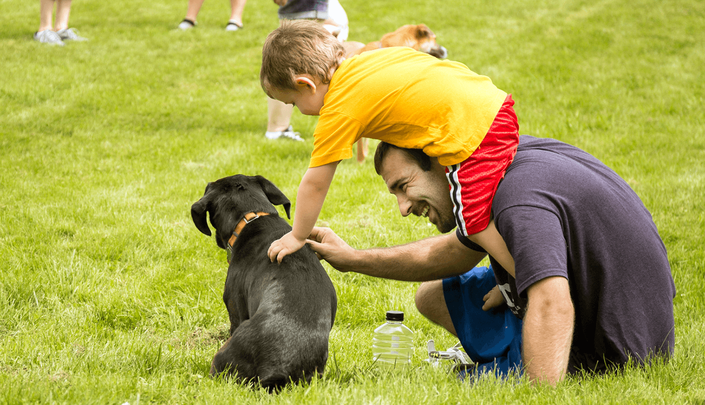 Image of father and toddler petting a puppy at Dog Mountain, Home of Stephen Huneck Gallery