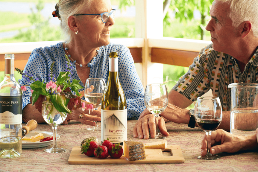 Image of cheese board and people talking at Lincoln Peak Vineyard