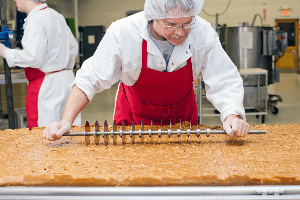 Image of man cutting toffee at Lake Champlain Chocolates