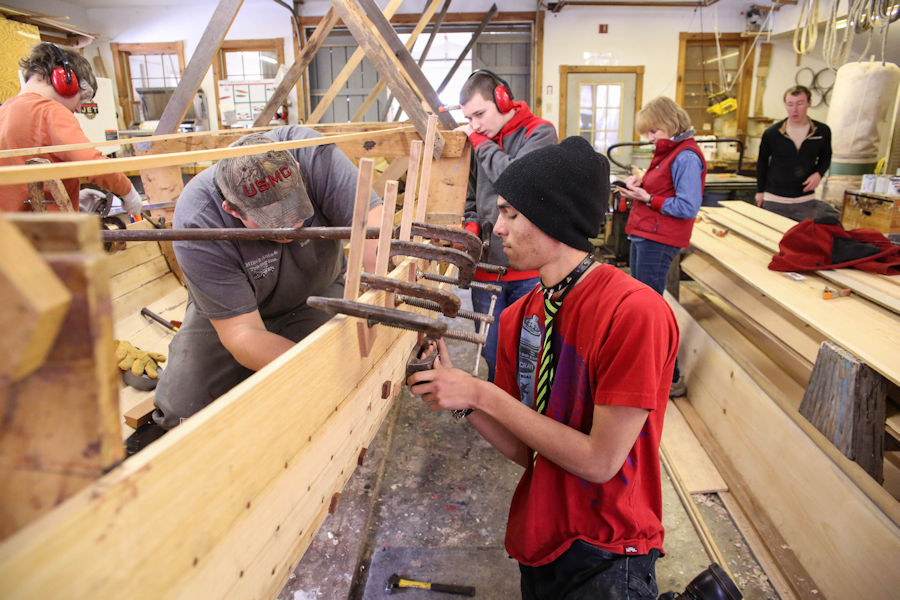 Image of high school students building a 32' row boat called a pilot gig.