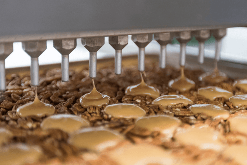 Image of a machine that puts caramel on walnuts