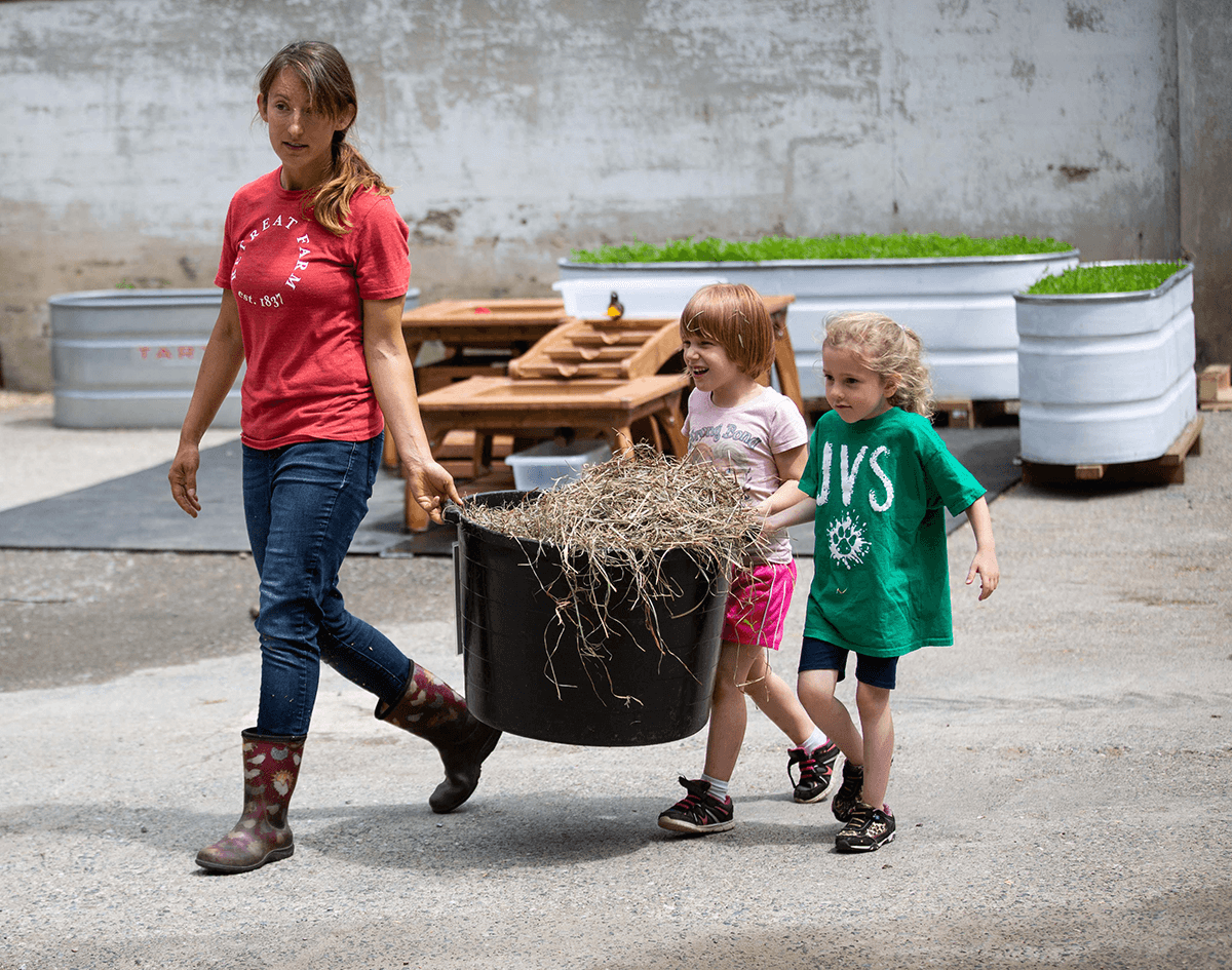 Image of woman and kids carrying hay.