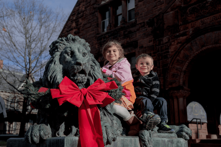 Image of kids on the lion wearing a bow