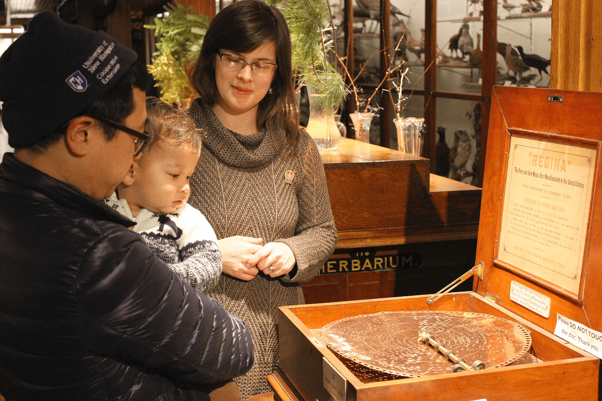 Image of family looking at antique music box