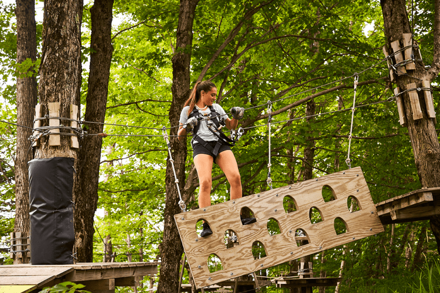 Image of a girl on ropes course obstacle