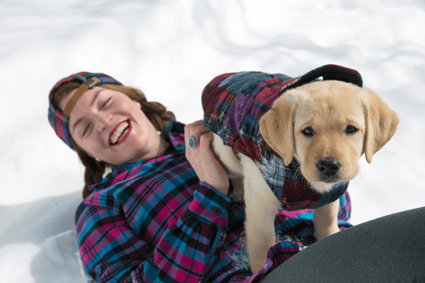 Image of woman laying on snow with puppy wrapped in flannel blanket