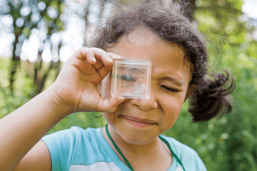 Image of girl looking at a bug in a magnifying box at Montshire Museum of Science