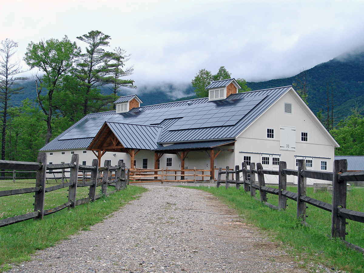Image of barn with clouds clinging to the hills behind it at Hildene, The Lincoln Family Home