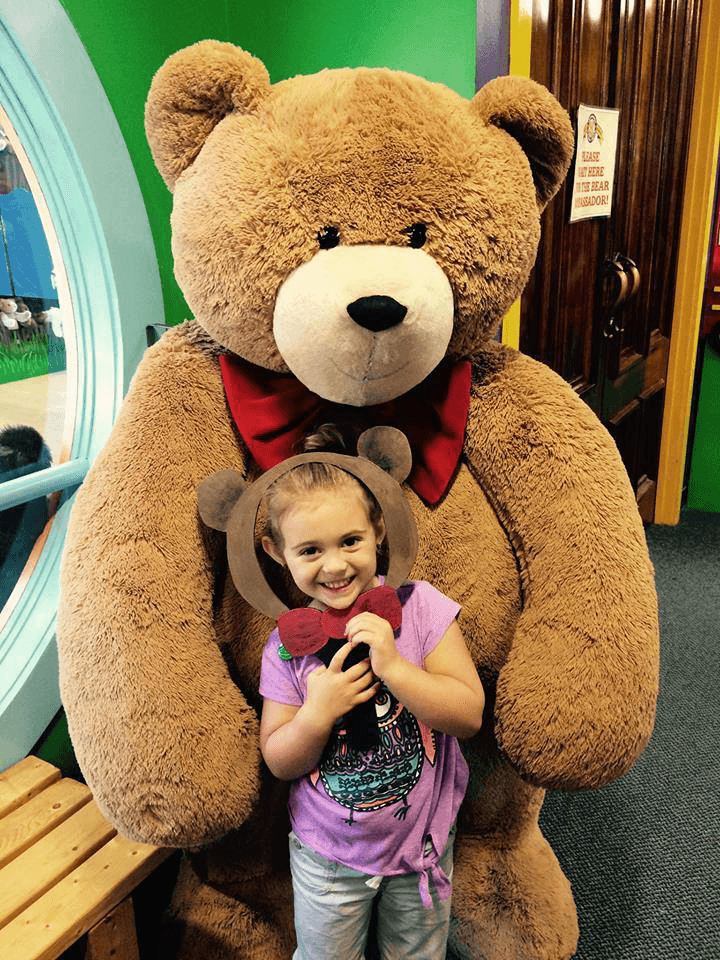 Image of a young girl standing with a large teddy bear sporting a red bow tie  at Vermont Teddy Bear Company