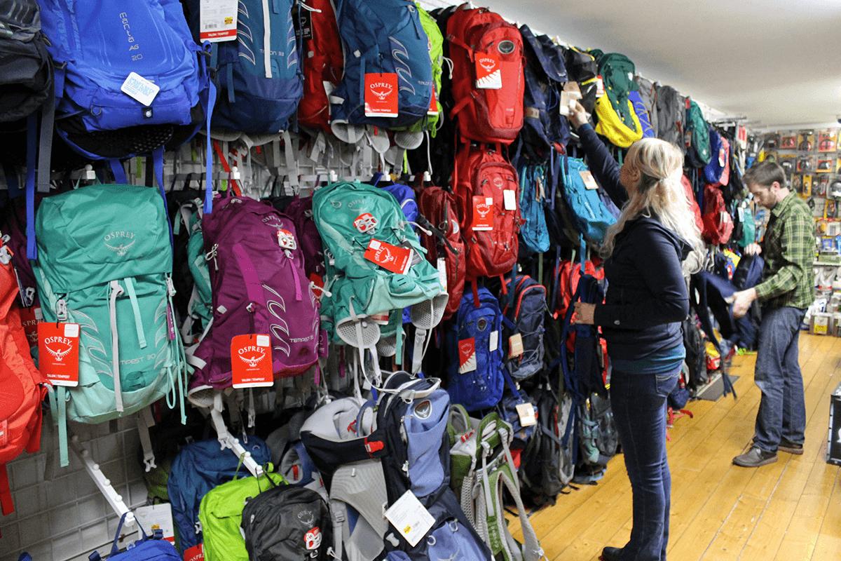 Image of woman shopping backpacks at Farm-Way
