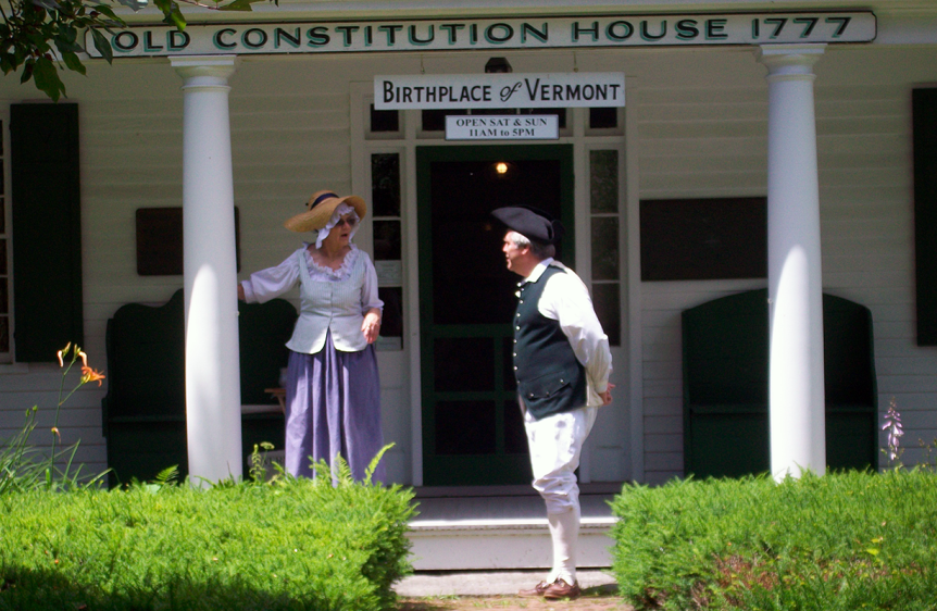 Image of reenactors talking on the steps of the Old Constitution House, a Vermont State Historic Site