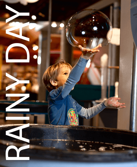 Image of a boy playing with a soap bubble. Things to do on a rainy day in Vermont.