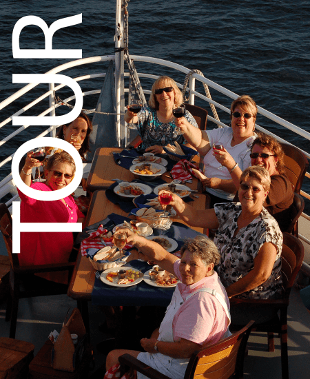 Image of people at a table on the deck of a boat. Boat rides and train rides in Vermont.