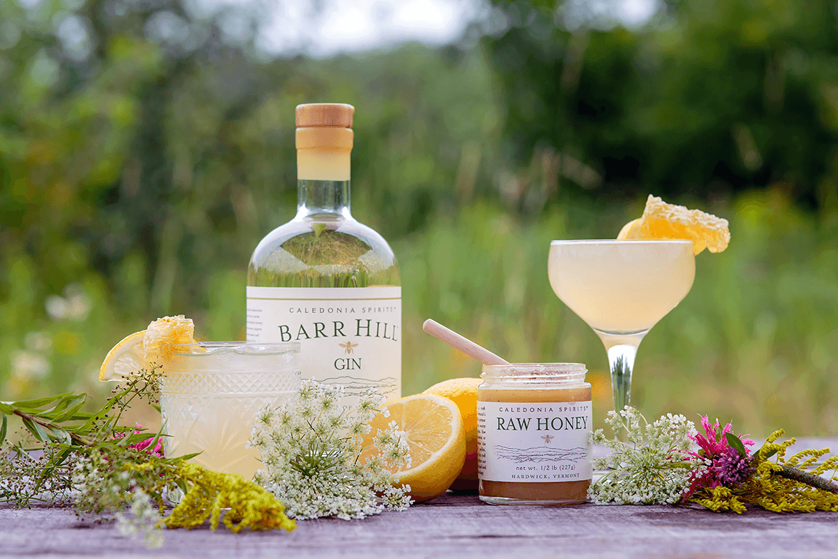 Image of Barr Hill Gin with honey, lemon, and flowers on a table.
