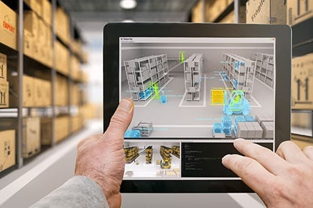 A small screen with a virtual storeroom is held by someone in a real-life storeroom to control logistics.
