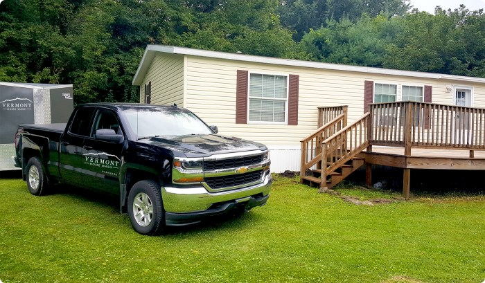 New black truck with Vermont Home Wash logo in front of power washed vinyl sided home