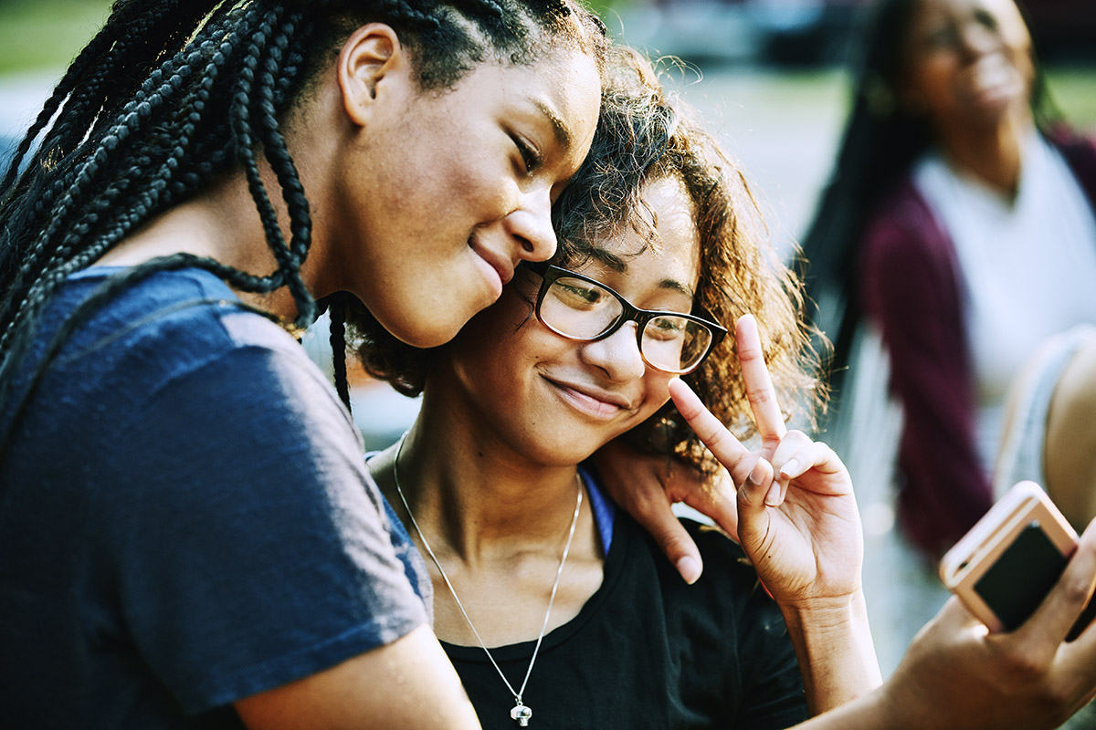 Smiling teenage friends taking selfie with smartphone on summer evening