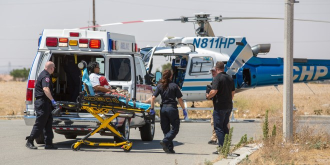 Paramedics prepare a woman with blood on her chest into the H-80 helicopter. (photo by Hugo C. Valdez, Victor Valley News)