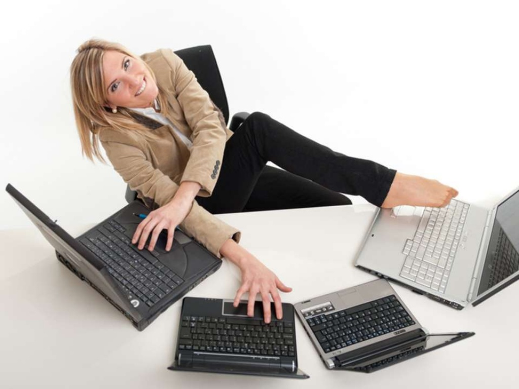 Femme avec plusieurs PC et son pied sur l'un d'eux