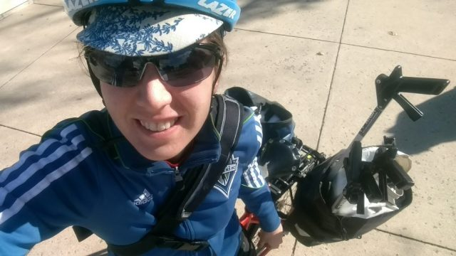Selfie of a woman in a bike helmet, blue Seattle Sounders jacket and messenger bag. There are handles of four trash grabbers in the lower right sticking out of a bike pannier.