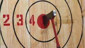 Axe stuck in bullseye on wood with target painted on it